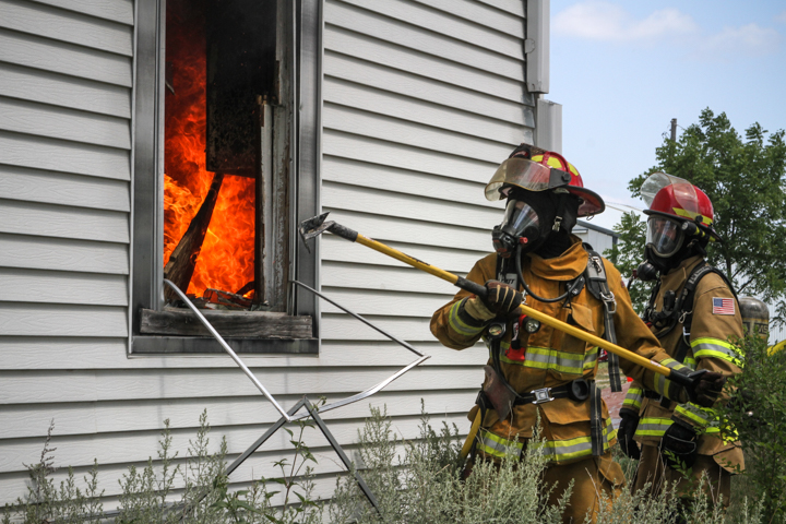 Kennard firefighter Ryan Coufal, left, and Qrlington firefighter Nick Kaup break out a window during practice burn.