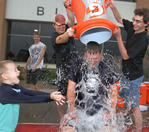 Dan Hutsell takes another bucket of ice and water  to the delight of Dan's  young son