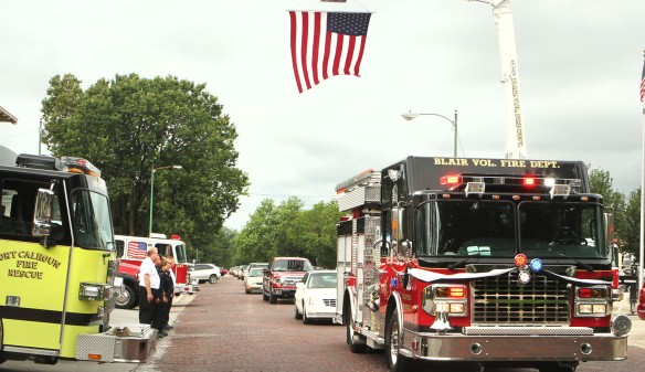 Donald L. Kuhr funeral procession passes under an American flag in front of the Blair south fire station.