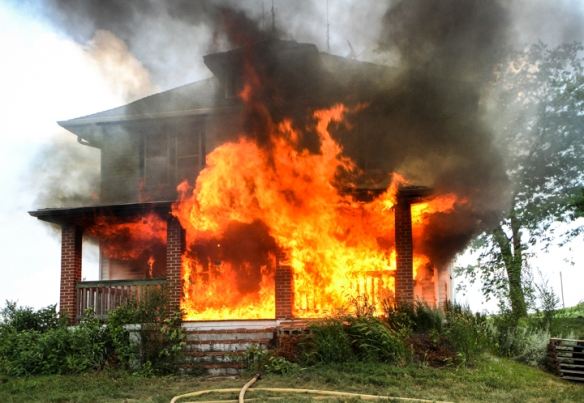 Fire leaps through windows and engulfs front porch on farmhouse used for practice burn.