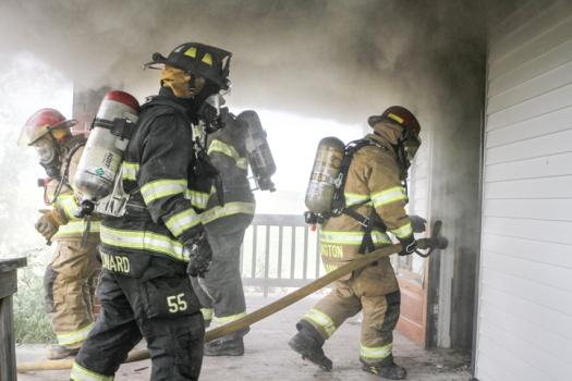 Arlington firefighter Matt Johann enters a house with a hose followed by Blair firefighter Joe Leonard.