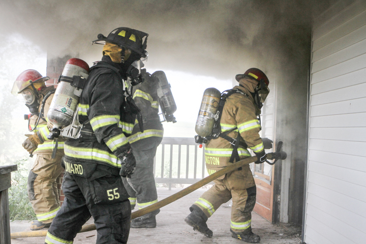 Arlington firefighter Matt Johann enters a house with a hose followed by Blair firefighter Joe Leonard.