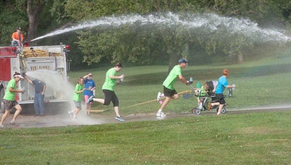 Runners sprint through spray provided by Blair Volunteer Fire Departmenr personnel.