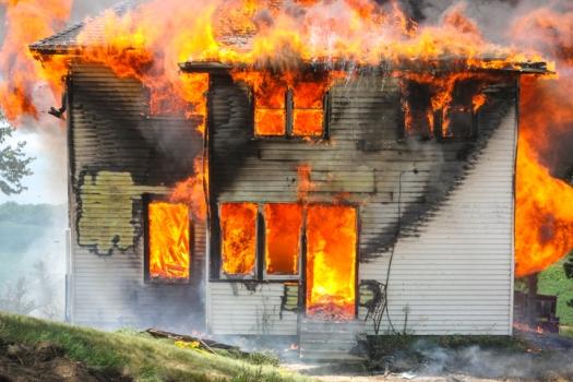 Fire engulfs the rear entrance of the farm house during practice burn near Arlington.