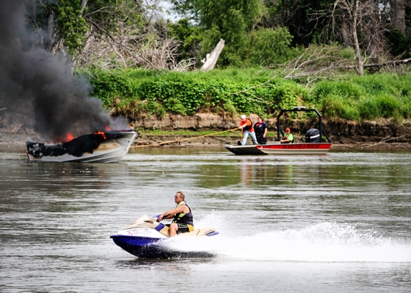 A jet-ski rider travels  up river in the foreground as Blair fire fighters pull a burning boat to shore in the background.