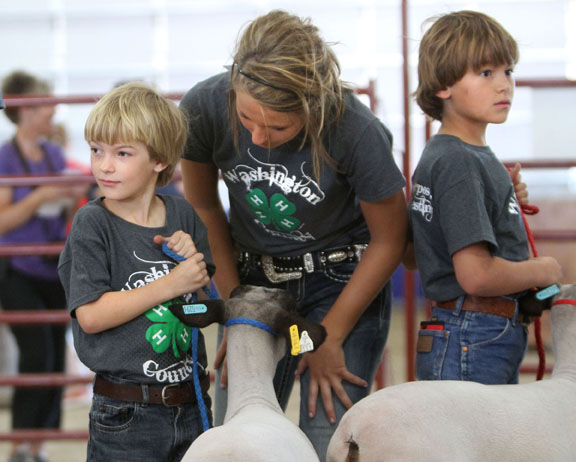 Paige Depperman assists Jonas Neuvirth while brother Hudson Neuvirth waits to show his lamb.