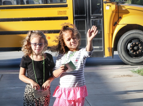 West kindergarten students Kalli Jordan, left, and Mariah Moore wave after getting off the bus Monday at Deerfield Primary School.  Students from West Primary School are being shuttled from West to Deerfield or North while repairs are completed at West due to the damage from the June 3 hailstorm.  Thirty-five students rode the shuttle Monday morning.