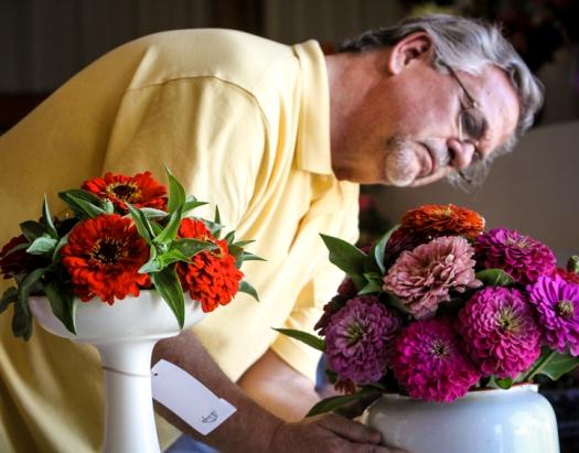 Floriculture judge Kent Stork scrutinizes a vase of cut flowers.