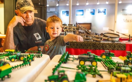 Larry Pfeifer watches as Mason Newman points to a favorite miniature tractor.