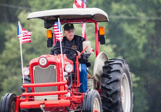 Lloyd Olson drives his 59 Ford Taskmaster tractor in the rain during the morning tractor ride.