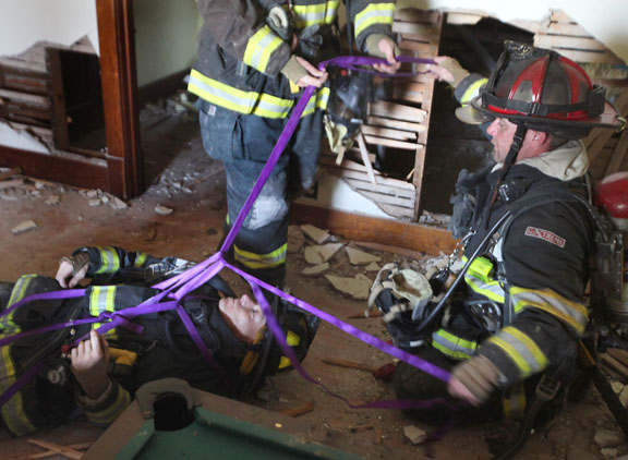 Blair firefighter Joe Leonard portrays a hurt fireman as Blair firefighers  riley Schonefilde and Heath Reyzlik domonstrate how to use webbing to pull Leonard to safety.