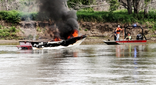 Blair Fire fighters tow aa burning boat to shore Saturday on the Missouri reiver.  Crews from Blair, Fort Calhoun, and Missouri Valley  responded to the boat fire.  No one was injured.