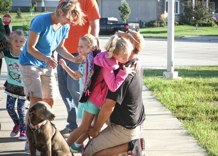 Daughters Brooklyn and Ryleigh share hugs with mom and dad  as they arrive at Deerfield on the first day of school.
