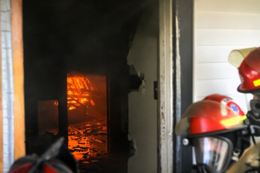 Fire fighters study the smoke as fire burns in rear of house.