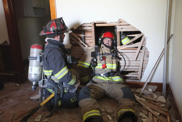 "Arlington firefighter Ryan Bosshart practice a ""swim"" technique to climb through a hole in a wall during survival training prior to the practice burn."