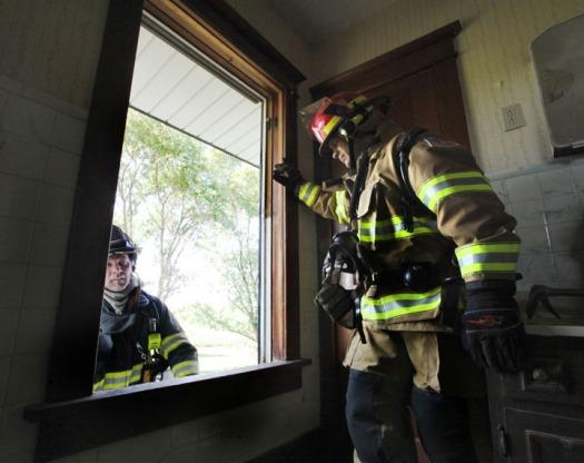 Blair firefighter Heath Reyzlik, left< demonstrates a window exit while Arlington firefigher Matt Johann look on Sunday, prior to a practice burn eas of Arlington.