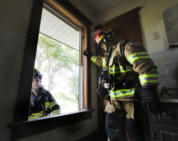 Blair firefighter Heath Reyzlik, left< demonstrates a window exit while Arlington firefigher Matt Johann look on Sunday, prior to a practice burn eas of Arlington.