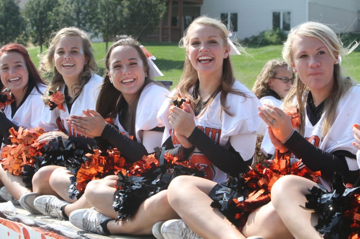 Dance team waves from flatbed during homecoming parade.