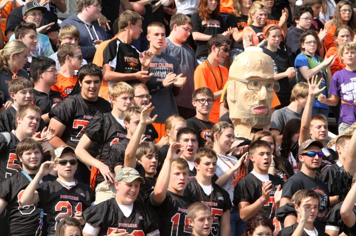 Fort Calhoun cheering students with oversize paper mache head of track coach and history teacher Brad Hatcher.