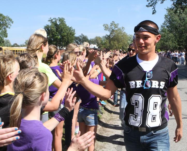 Fotball team gives  elementary kids high fives.