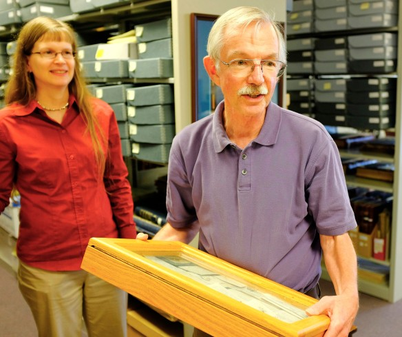 Jill Hennick, director of the Danish American Archive and Library, and Tim Jensen, DAAL board member and volunteer, display shadowboxes containing Danish heritage artifacts.