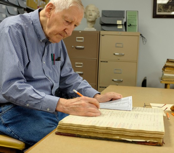 Verlan Hanson checks  information recorded from Danish Brotherhood registration ledgers.