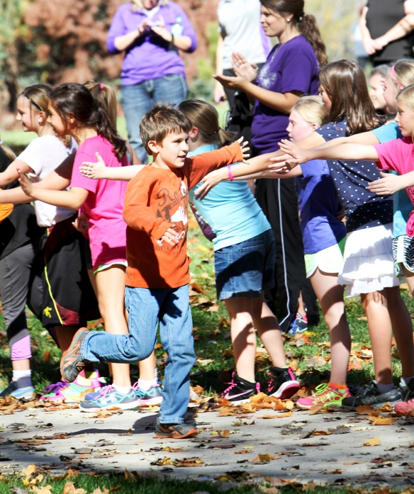 Classmates greet fourth grader Connor Mahaffey as he runs toward the finish.