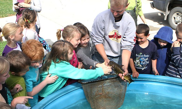 Fort Calhoun first grade students touch the smooth flesh of a catfish that Game and Parks biologist Matthew Grunterad holds. .