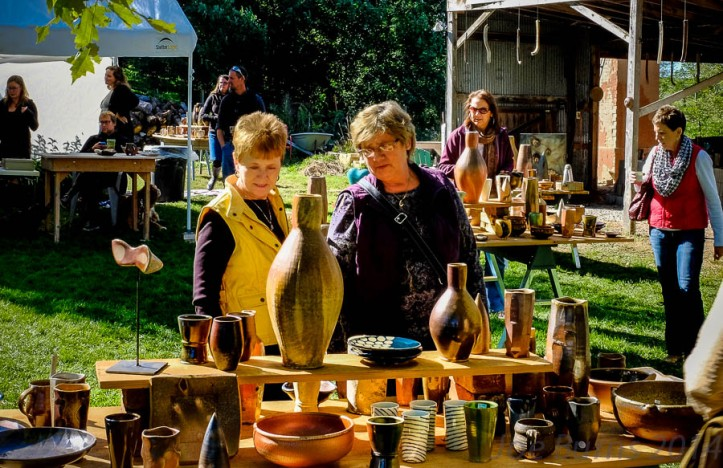 Diane Stolz and Nancy Meyer browse through tables of ceramics.