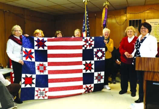 Jill Vacek at podium and quilters from left, Myrna Verecruysse, Laura Shaw, Katy Adams, Diane Stier and Betty Lunn present Pat Hunsche with a Quilt of Valor for her service to her country and to Washington County Veterans groups.