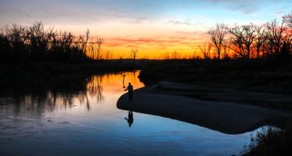 Fisherman casts his line at Boyer Chute at Sunset.