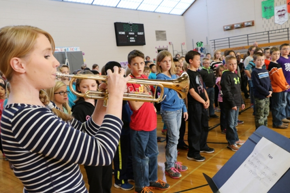 Instrumental Music teacher Courtney Baker plays taps at the Arbor Park Veterans Day ceremony.