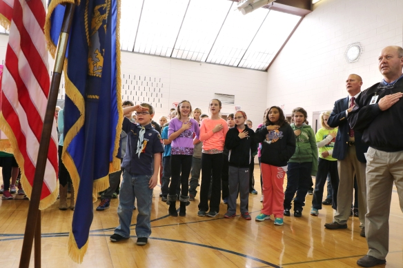 Fifth grader and Cub Scout Sam Dowdy leads Arbor Park Intermediate School in prior to the school's Veterans Day ceremony. At right, Principal Mike Janssen and teacher Norm Svobodfa join in. Svoboda is also a veteran who served in the Army National Guard for 12 years.