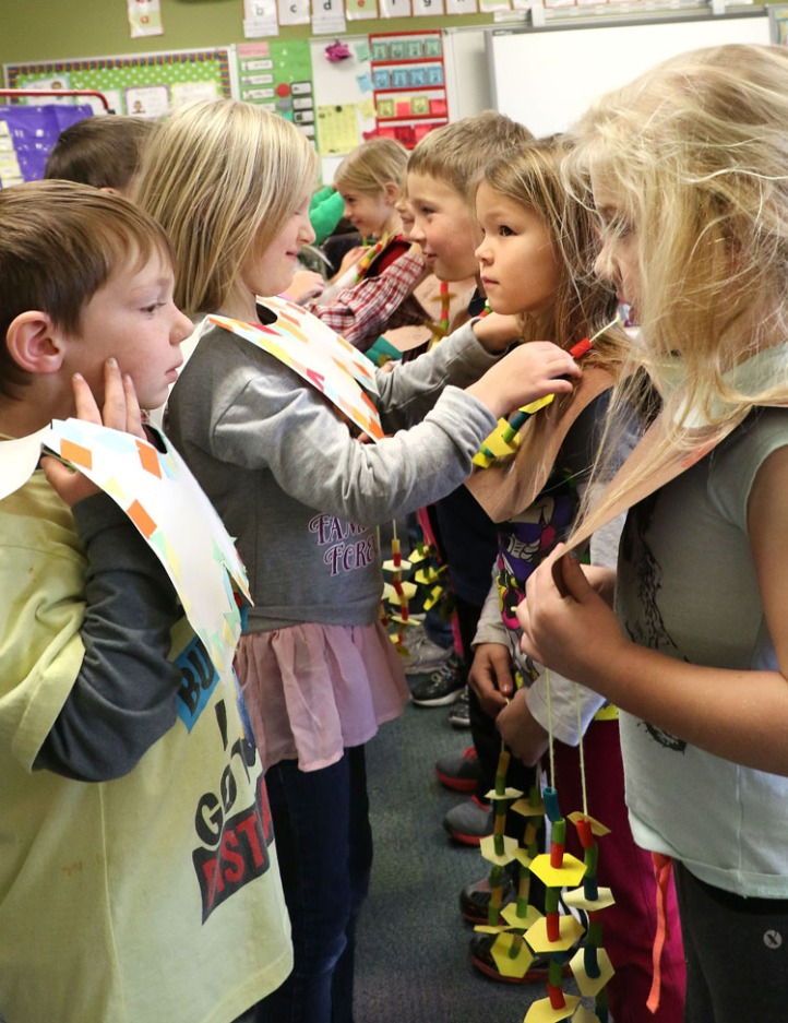Callie Arnold's students dressed as pilgrims and Native Americans share friendship bracelets.