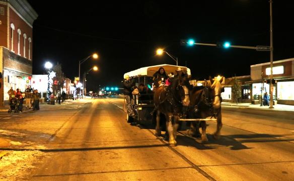 People riding along Washington Street on  horse drawn wagaon