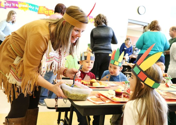 Dressed in Native American clothing, Lisa Lindau serves up green beans to her daughter Lucy.  Deerfield kindergarten students learned about Thanksgiving and shared a Thanksgiving feast on Monday.