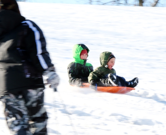 McCoy and Tommy Scott sled down the hill at Ralph Steyer Park on Sunday.