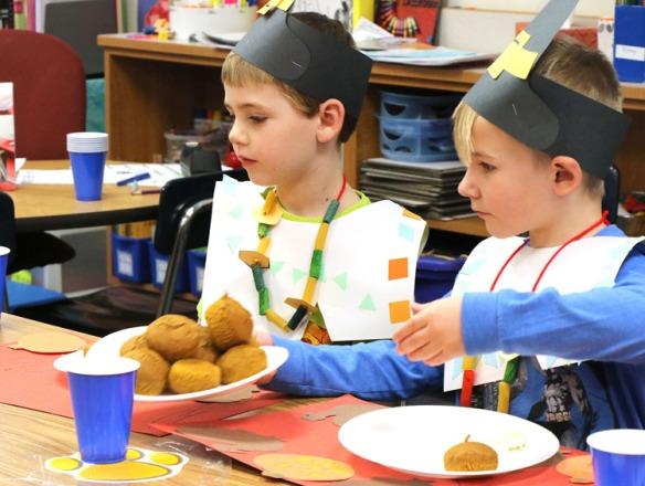 Liem Taylor and Braxton Davis pass a plate of home made pumpkin muffins.