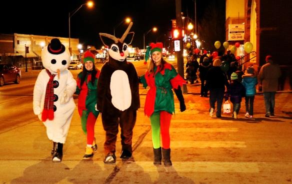Snowman Jacob Hank Sorensen, Elf Carli Pfeil, Rudolf Jacob Garder, Elf Whitney Aman walk along Washington Street Thursday.