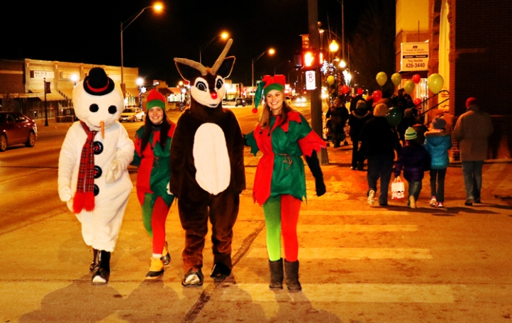Snowman Jacob Hank Sorensen, Elf Carli Pfeil, Rudolf Jacob Garder, Elf Whitney Aman walk along Washington Street Thursday.