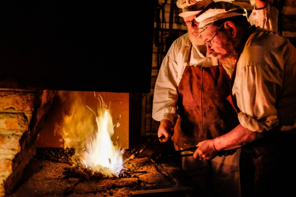 Doug Appel and Dean Slader fire metal rods at the forge  in the Blacksmith's shop to makel tent stakes.