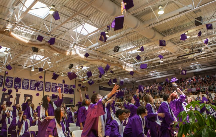 Graduates of the class of 2014 throw hats into the air.