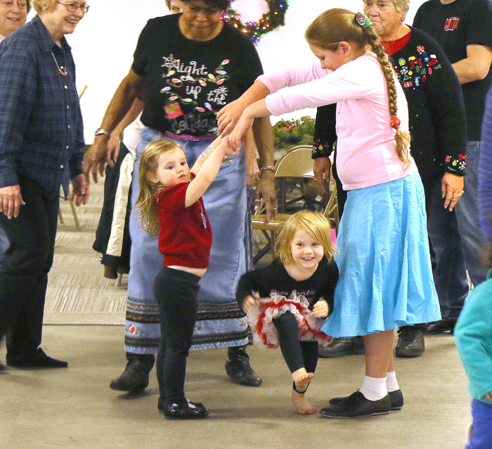 Kaitlyn Gochanour and Freya Schogren make an arch for Bella Nelson and dancers at the Barndance held at St. John's Schwertly Hall Saturday evening December 13.