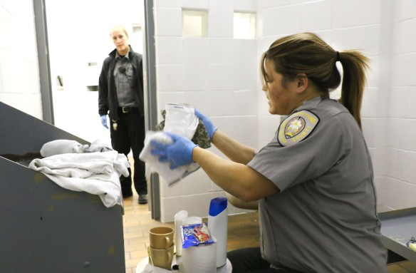 Washington County Jail corrections officer Jenny Meyer searches a cell Saturday Night while officer Shawna Brown watches.