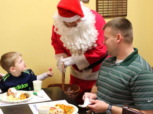Santa visits with Ben and son Brock Deutschman at Christmas for the Coat.