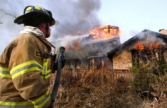 Fort Calhoun fire fighter Dan Mallory sprays water to control the spread of flames to trees an d brush surrounding the burning house.  Fort Calhoun and fire departments from the surrounding area took part in the practice fire on Saturday.