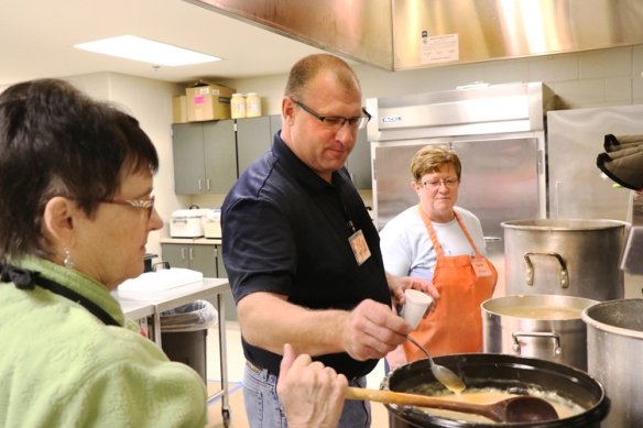 Jaimie Anderson testes gravy prepared by Carol Hartvigsen and Shirley O'Brien. Hartvigsen is a member of First Lutheran Church and O'Brien is a member of St John the Baptist Parish in Fort Calhoun.