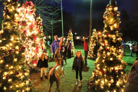 Odvodey family from left Scarlett, Joel holding Penelope,  Elise and Becky wander through  lighted Christmas trees in West Market Square in Fort Calhoun.