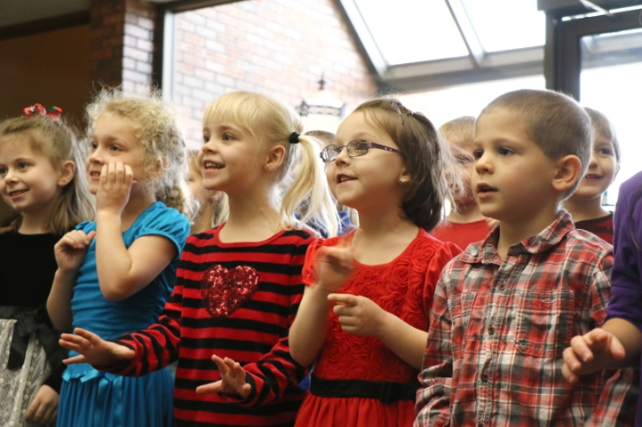 South School kindergarten students Valerie Jensen, Mia Kern, Amelia Boswell, Emily Roberts, and Zach Matney sing at the Washington County Bank on Tuesday.