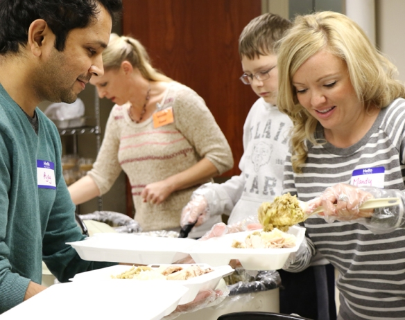 Ajay Gurdev  holds a takeout  container  and Mandy Tamisea fils with turkey and all the fix in's.  In the background are Wendy Rand and James Crotty.  Rand, who  is a member of Country Bible  was one of eight chairman who help organize and [put on the dinner.  The volunteers typically serve around 200 takeout orders in addition to 500 or more who eat in.